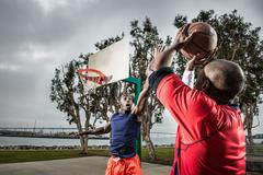 Young basketball players jumping to score hoop Stock Photos