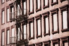 Fire escape on brown building - stock photo