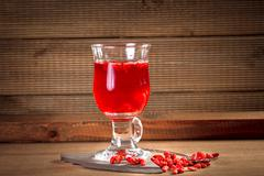 Glass healing infusion of goji berries and dried berries nearby. - stock photo