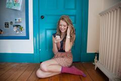 Teenager sitting in front of blue door, using mobile telephone Stock Photos