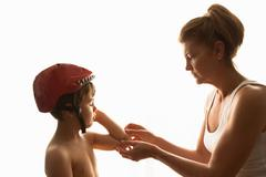 Mother putting adhesive plaster on son's elbow Stock Photos