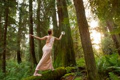 Mature woman standing on log in forest - stock photo