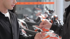 Close up of buyer getting motorbike key Stock Footage