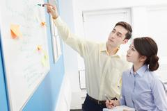 Colleagues using white board with adhesive notes - stock photo