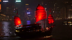Hong Kong World famous skyline at night with red ancient sail boat Stock Footage