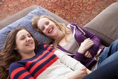Girls lying on sofa giggling - stock photo