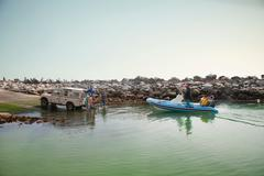Small group of men landing dinghy in harbor - stock photo