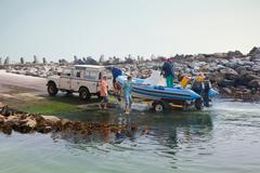 Small group of men landing dinghy onto trailer in harbor Stock Photos