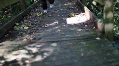 Kid running fast in a park crossing a wooden bridge covered of withered leaves. - stock footage