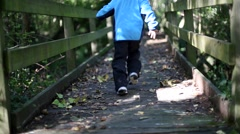 Kid running fastly in a park crossing a wooden bridge. Stock Footage