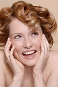Young woman with curly red hair laughing - stock photo