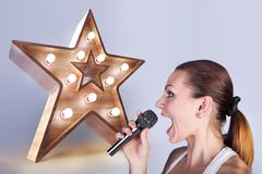 Girl with a microphone on the background of sign star. Stock Photos
