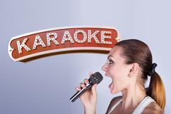 Girl with a microphone on the background of sign of karaoke. Stock Photos