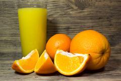 Oranges and fresh orange juice on wooden background Stock Photos