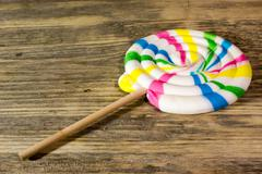 Round spiral color candy on wooden background. Stock Photos