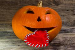 Pumpkin for Halloween is holding in his mouth a red heart for Valentine day o Kuvituskuvat