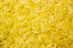 Grain yellow parboiled rice as background Stock Photos