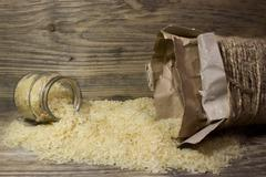 Rice grains in glass jar on wooden background - stock photo