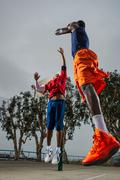 Young basketball players jumping to score - stock photo