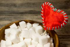 Sugar cubes and a red love heart on wooden background Stock Photos
