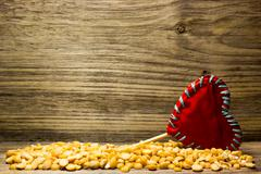 Crushed dried peas and a red love heart on wooden background Stock Photos