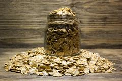 Wheat flakes in glass jar on wooden background Stock Photos