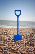 Blue spade stuck into pebbles on beach Stock Photos