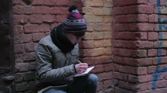 Romantic young man sitting alone in deserted place, writing poetry in notepad Stock Footage
