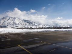Empty parking lot with snow covered Wasatch Mountains in background, Salt Lake Stock Photos