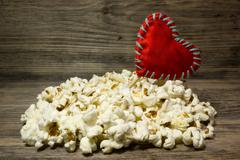 Popcorn and red heart love on wooden background - stock photo