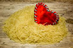 Small dry pasta noodles and red heart love on wooden background Stock Photos
