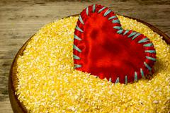 Corn grits and red heart love on wooden background Stock Photos