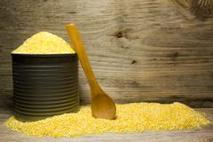 Corn grits and wooden spoon in tin on wooden background - stock photo
