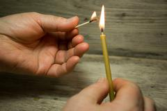 A lighted match in his hand and the candle, Matches with blue heads on wooden - stock photo