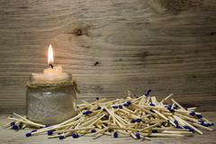 A lighted candle, Matches with blue heads on wooden background - stock photo