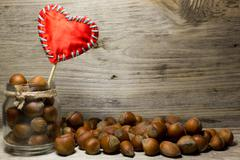 Hazelnut in shell in glass jar  and red heart love on wooden background Stock Photos