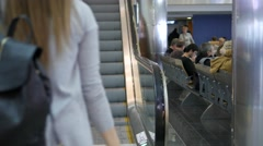 Woman with suitcase and rucksack rises on escalator in airport Stock Footage