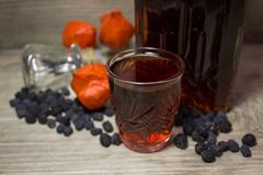 Glass and carafe with red alcoholic beverage, dried black berries of the bird Stock Photos