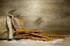 Bread sticks with salt in Kraft box on wooden background Stock Photos