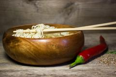 Instant noodles in a wooden bowl with chopsticks. Wooden background and red p Stock Photos