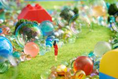 Figurines on pretend grass with marbles Stock Photos