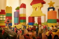 Toy cars and figurines in pretend plastic block town Stock Photos