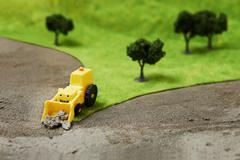 Toy digger on model landscape - stock photo