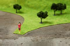 Figurine on pretend grass with trees Stock Photos