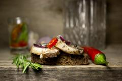 Slices of bacon with spices with rye bread. Kraft paper as the background. Stock Photos