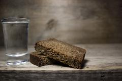 A glass of vodka and a slice of rye bread on a wooden table. - stock photo