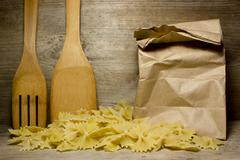 Noodles Farfalle butterflies and wooden spoon on wooden background. - stock photo