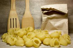 Noodles seashells and wooden spoon on wooden background Stock Photos