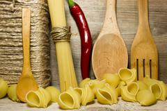 Noodles seashells and wooden spoon on wooden background - stock photo