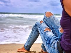 Legs of woman sitting on coast near ocean with waves. Hot dog leg selfie. Stock Photos
